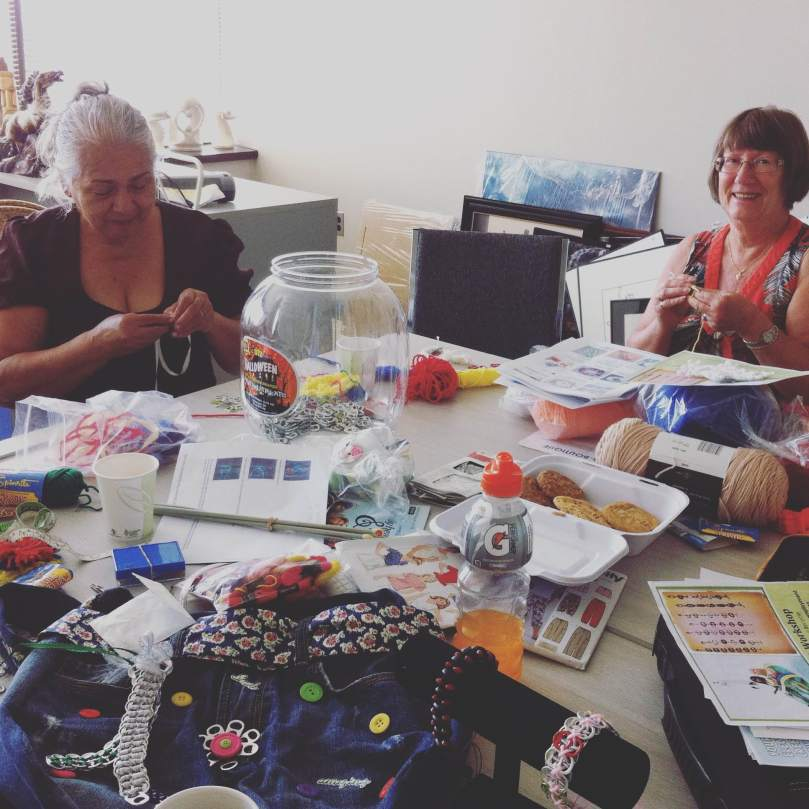 Women work on their crafts using recyced materials for the Eco Arts program
